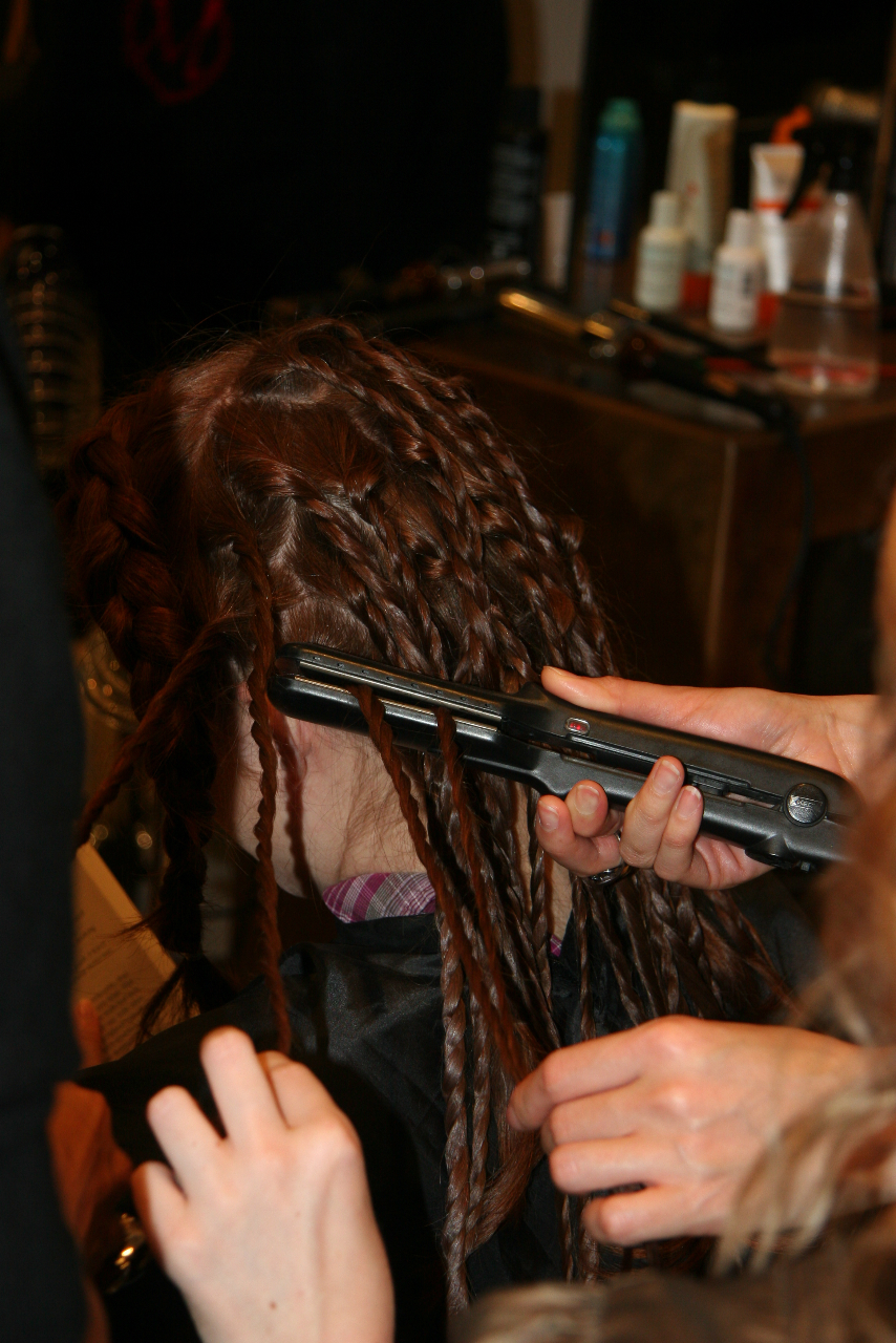 Hair being braided with a curling iron