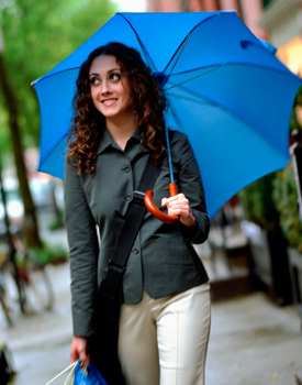 Woman with long curly hair holding an umbrella