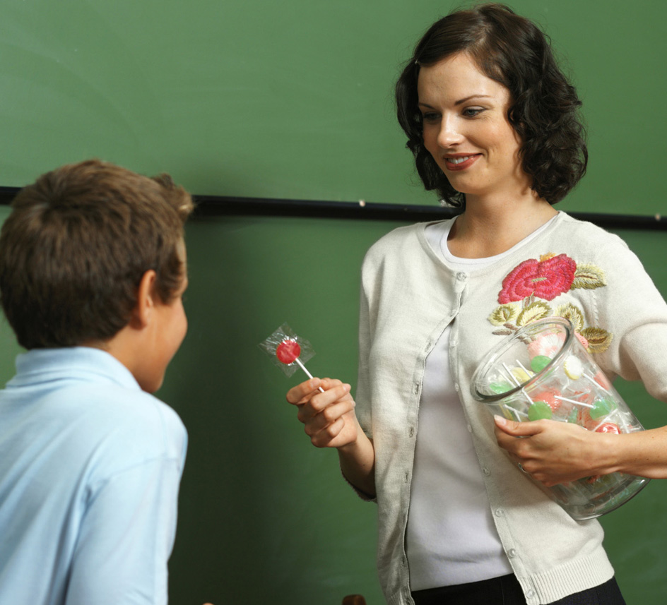 Teacher offering student a lillipop