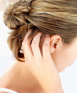 Woman scratches itchy scalp