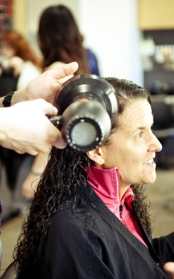 NaturallyCurly's Michelle Breyer has her hair diffused by an ARROJO stylist.