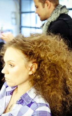 A Matrix model with her teased out curls before final styling.