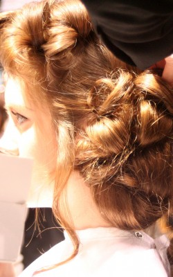 A stylist arranges pincurls into a low bun and a bouffant