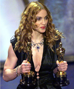 Madonna holds two Oscars as she presents the award for Best Song at the 1998 Oscars