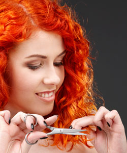 Girl with red curls trimming her hair