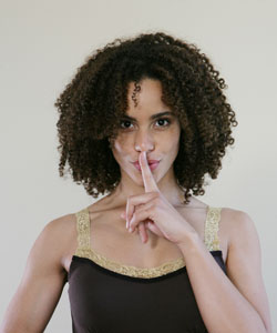 Lady with curly hair with a finger over her lips