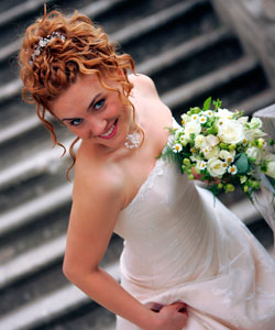 Bride with curly red hair smiling and looking up
