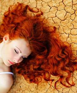 lady with Curly red hair sleeping in desert