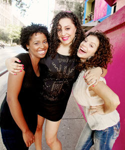 three young women smiling and laughing with curly, coily and wavy hair