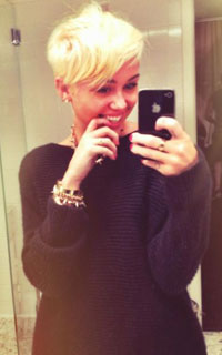 Miley Cyrus take a picture of her new haircut