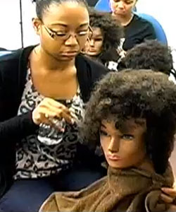 Lady learning to style naturally curly hair on a hairdresser mannequin head
