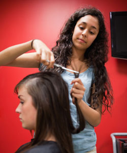 young woman with curly hair cutting a client's hair