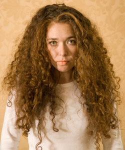Lady with big, curly, red hair looking straight ahead and serious