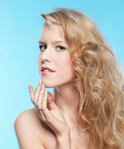 Lady with blonde wavy hair looks out at you