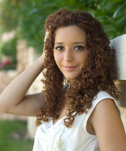 young lady smiling with her hand in her brunette curls