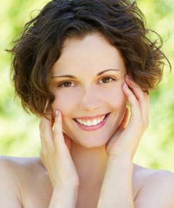 Lady with wavy brown hair in a bob hairstyle smiling with her hands cupping her face