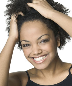 Lady with coily hair smiling with hands in her hair