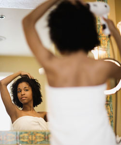 Lady looking in the mirror and drying her coily hair