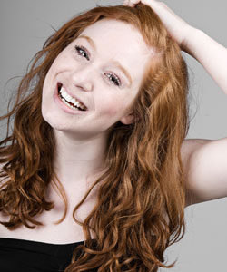 Lady with red wavy hair laughing with her hand in her hair and her head tilted back