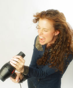 Lady with curly hair using her hair dryer as a microphone