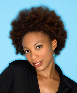 lady with coily afro smiling