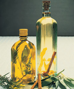two glass bottles of oil with whole herbs an spices