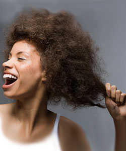 Lady laughing and pulling her big curly hair behind her