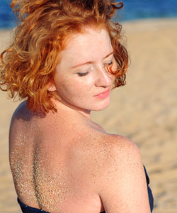 lady with red hair on the beach looking back over her shoulder