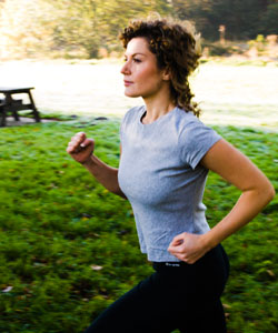 Lady with curly hair running in a park