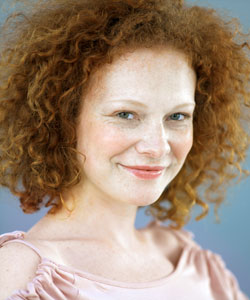 lady with curly red hair smiling