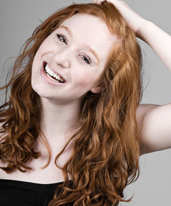 Redheaded young woman smiling with her hand on top of her head