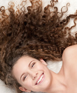 lady smiling with her curly hair spread out