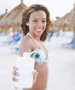 Young lady with wavy hair holding out sunblock and smiling