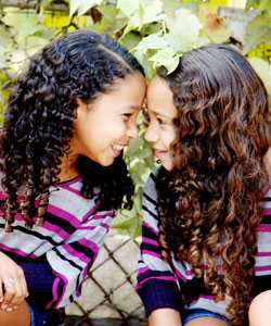 Two girls with curl hair smiling and putting their heads together