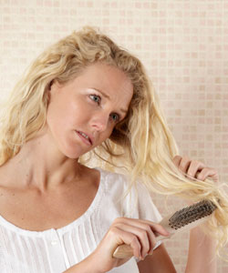 Lady with blonde wavy hair unsuccessfully trying to brush her hair