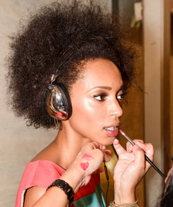 Model with afro hair listening to headphones and getting makeup done
