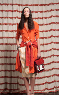 Model with crimped textured long hair wearing bright orange tones by Chris Benz