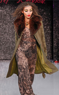 Model with textured hair wearing coat and dress by Betsy Johnson