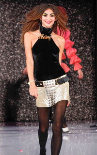 Model with curly hair wearing black halter top and mini skirt by Betsy Johnson