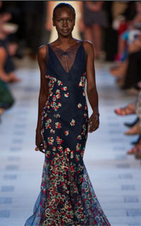 Model with short cropped coily hair wearing floral gown by Zac Posen
