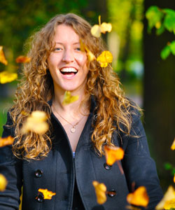 Lady with curly hair surrounded by falling autumn leaves