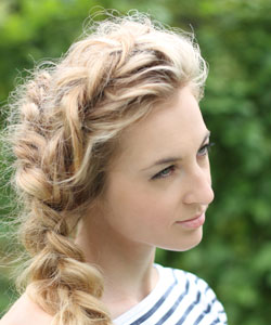 beautiful young lady with curly blonde boho style braid staring off into the distance