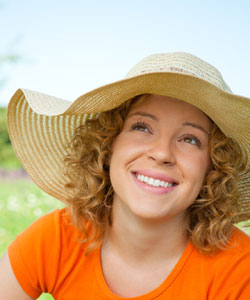 Lady wearing a hat over her curly blonde hair and smiling up at the sun