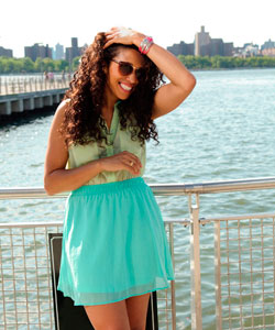 woman smiling with long curly hair standing by the waterfront with hand in her hair