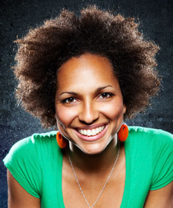 Woman wearing an afro and smiling brightly