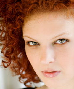 Woman with red curly hair staring seriously