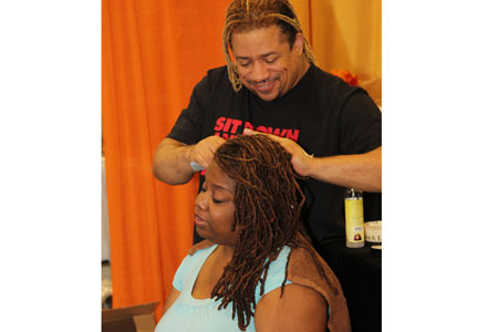 Stylist with loc'd hair styling a lady's loc'd hair