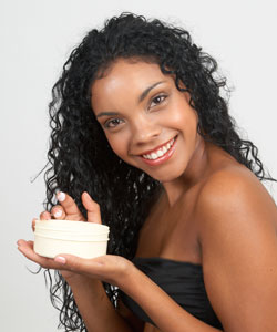 lady with curly hair carrying a tub of body cream
