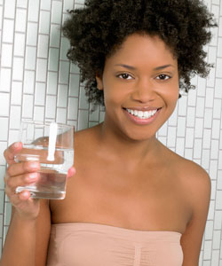 lady with coily hair holding water glass