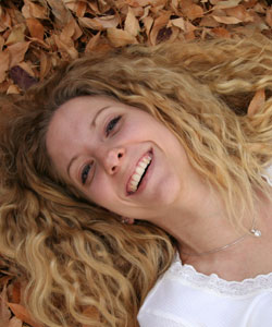 Lady with wavy hair lying in leaves and smiling
